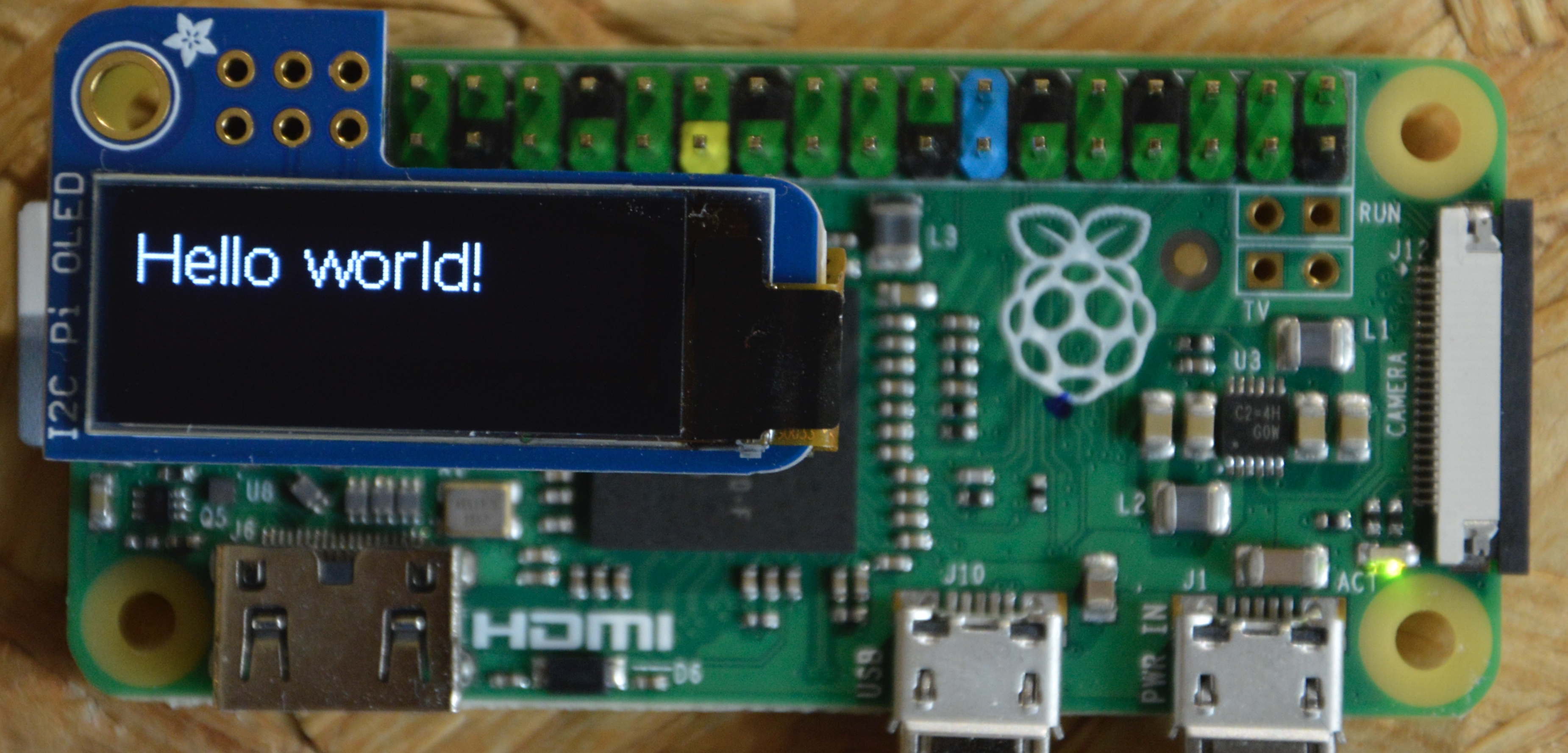 """Image of Raspberry Pi with PiOLED connected to it on which """"Hello world!"""" is visible"""