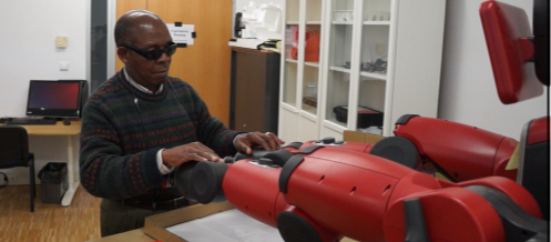Blind person touching a robot extended arm