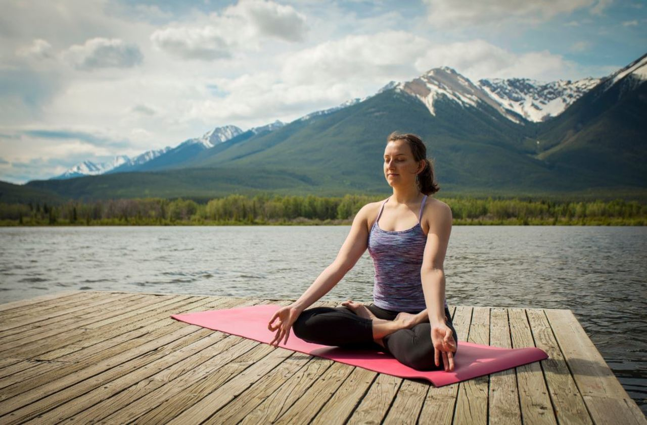 Lady meditating with mountains in background