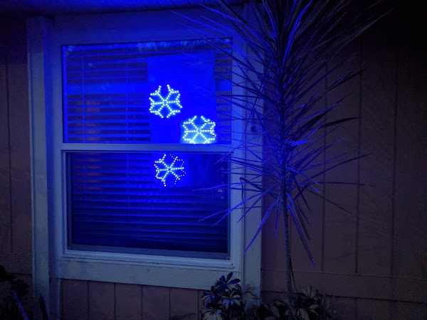photo of snowflake lights in window from the outside