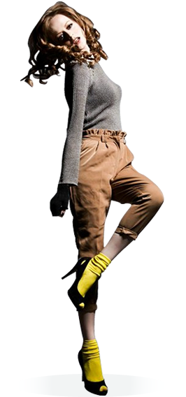 A female model with long curly brown hair wears a gray sweater, brown shorts, bright yellow socks, and black high heel shoes. She raises one leg, and tilts her head to the side