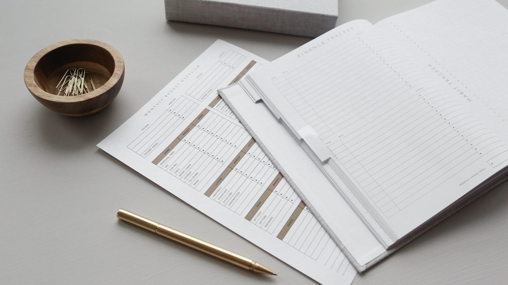 A paper planner and a brass pen