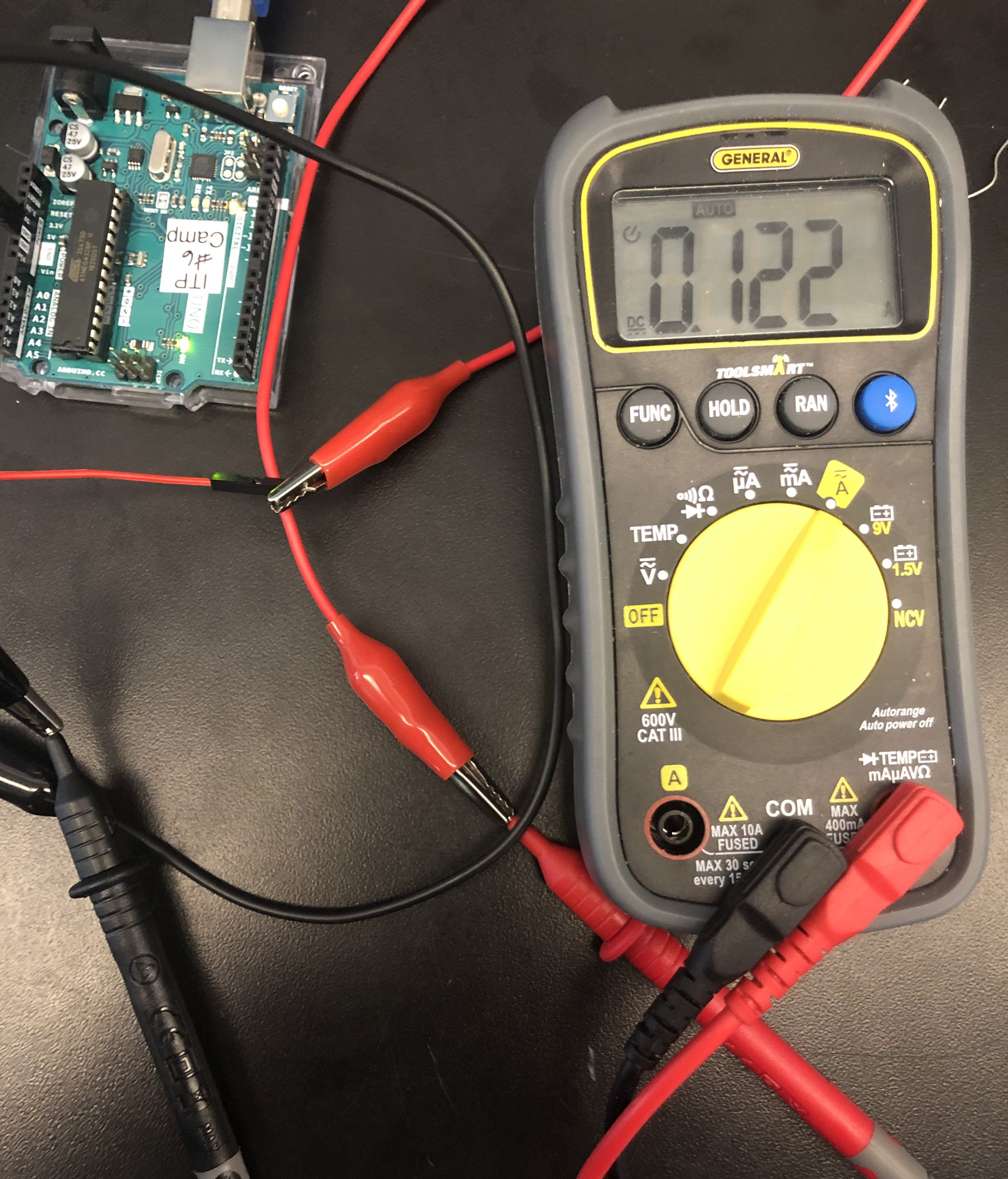 a multimeter showing 0.123 amps