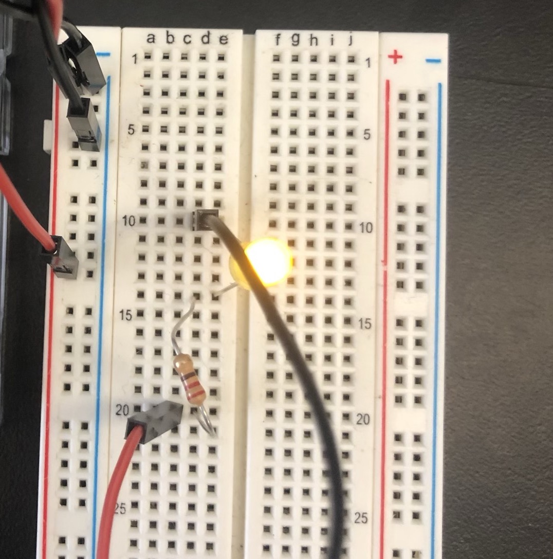 an LED wired into a breadboard with a 220 ohm resistor