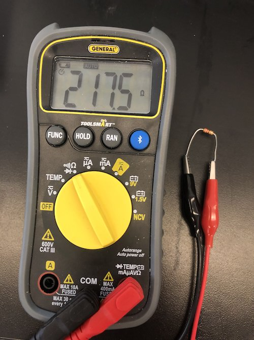 a multimeter measuring a resistor that reads 217.5 ohms