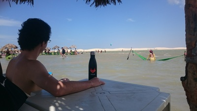 Ciro Santilli in a dune lake in Jericoacoara, Brazil with his GitLab bottle
