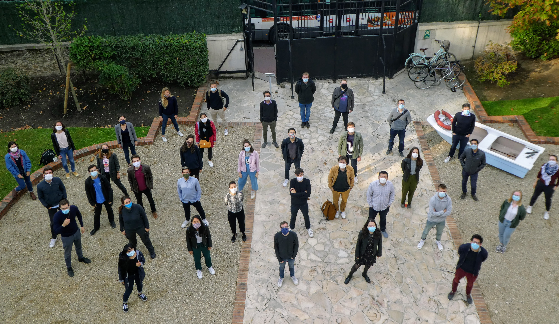 Photo d'une quarantaine de jeunes personnes dans une cour. Elles sont masquées et se tiennent espacées les unes des autres. Elles sourient derrière leur masque.