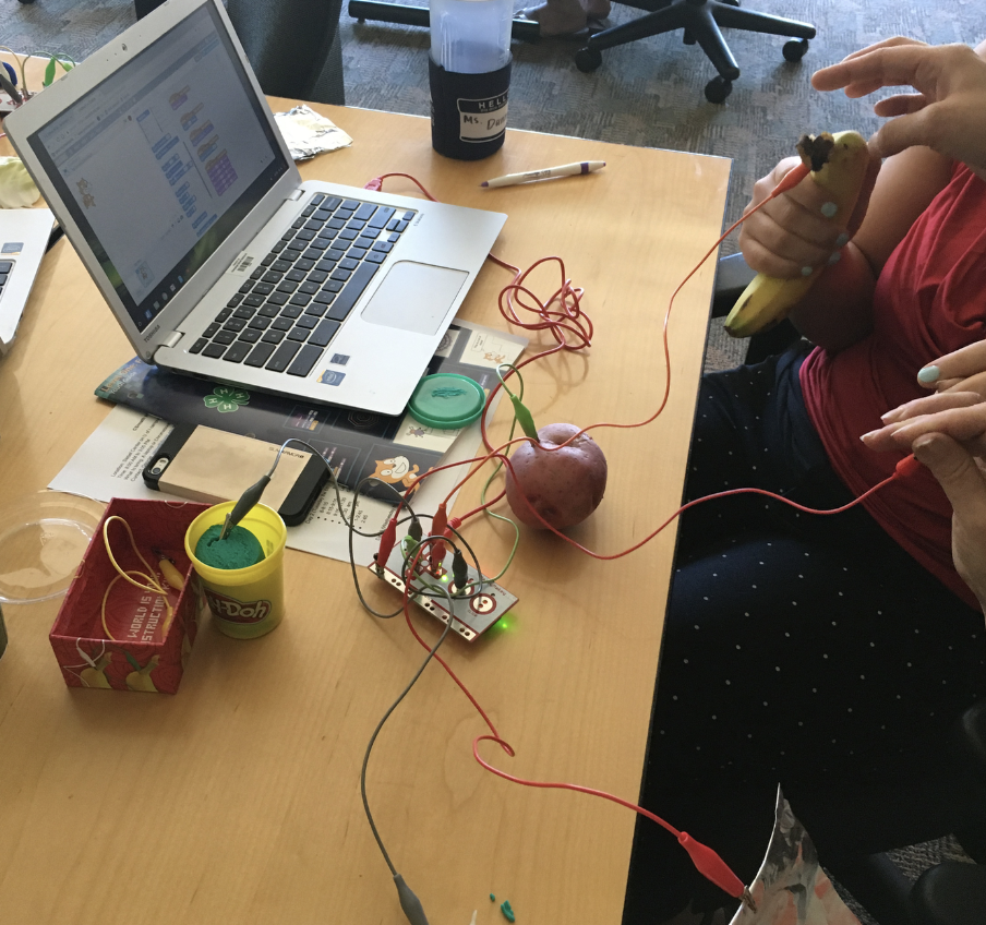 Children attaching a fruit to Makey Makey probes to turn them into musical instruments