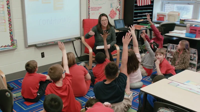 Video thumbnail: students raise their hands to answer a question as a teacher speaks