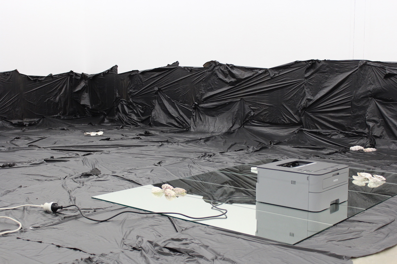 installation shot of printer on floor covered in  black plastic