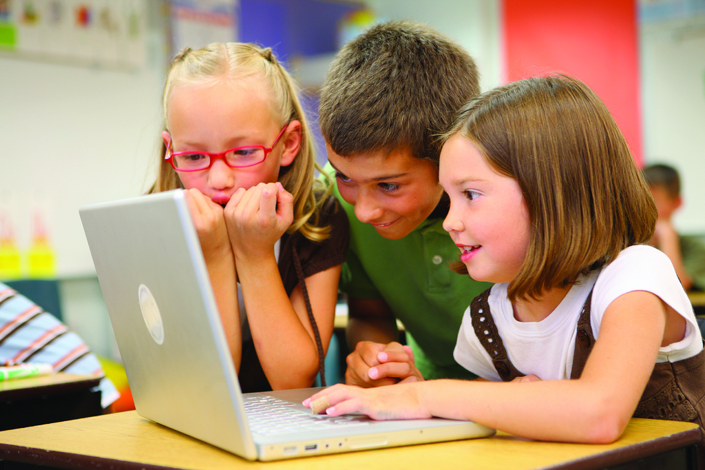 Excited looking kids at a laptop