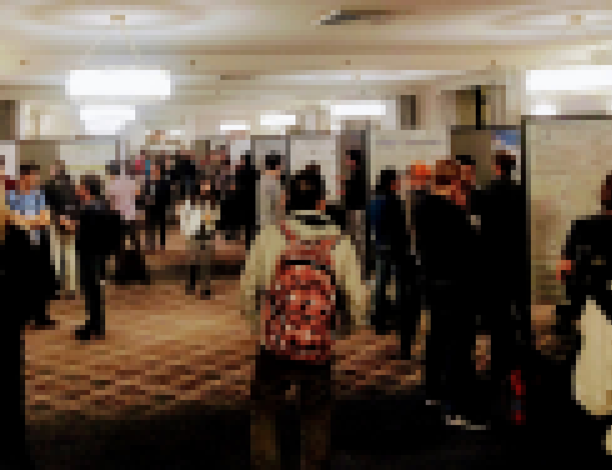 Image of people interacting at a conference poster session.