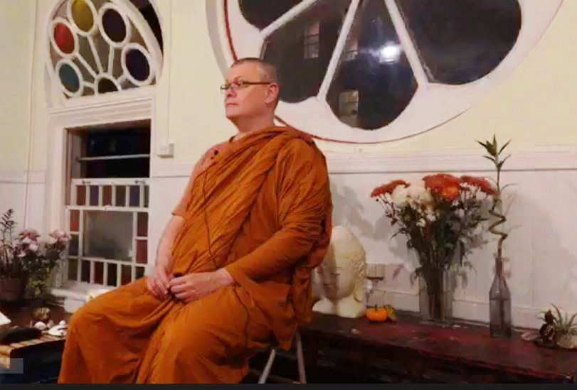 Bhante Sujato giving a dhamma talk in an old style building with pretty windows