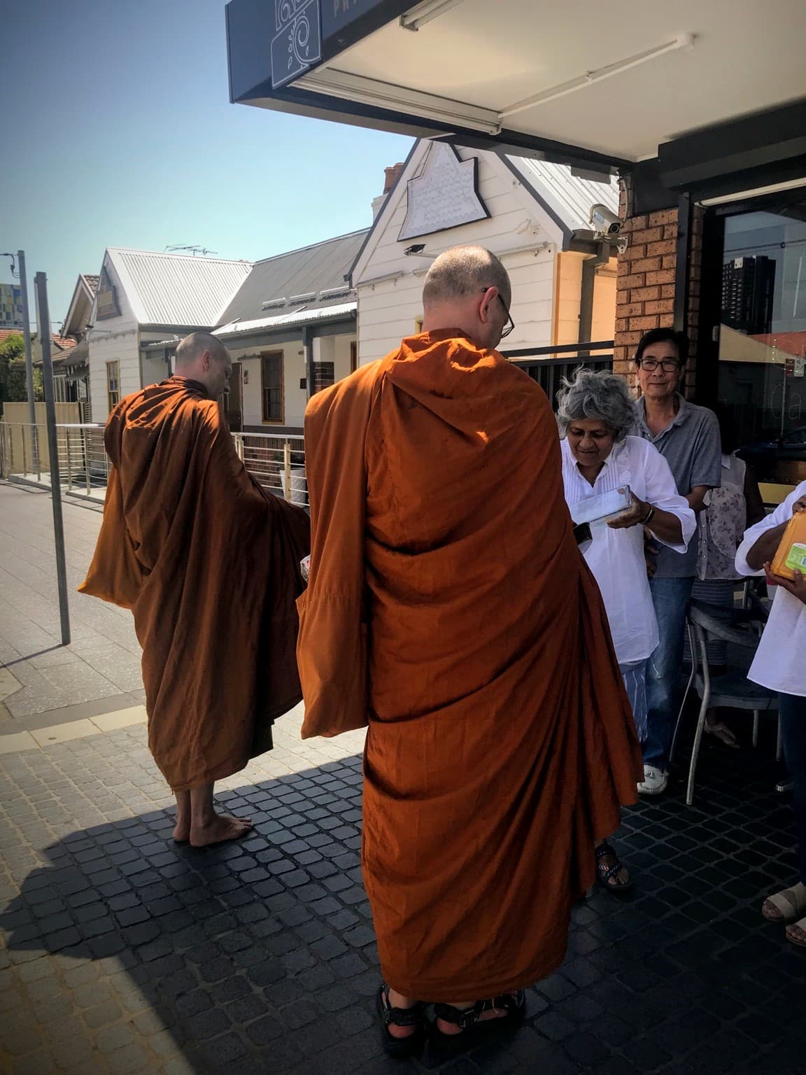 Photo of Bhante Sujato and Bhante Akaliko on almsround in Harris Park.