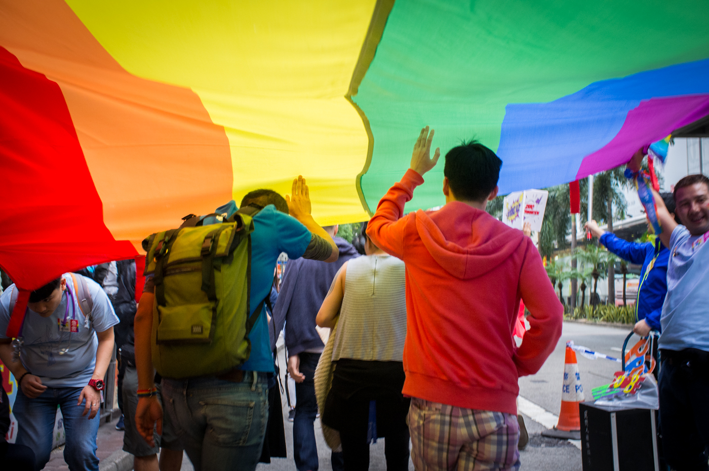 Two Chinese men with short hair walking under a long rainbow flag with one hand up