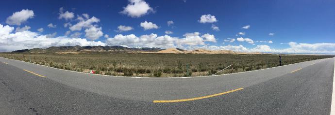 公路旁边的牧场,远处是沙漠和草场