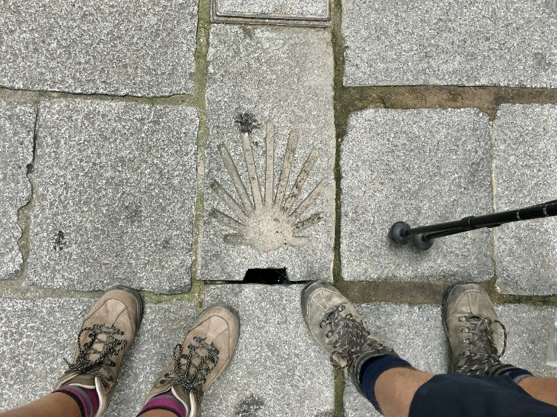 camino sign in stone floor with feet and poles