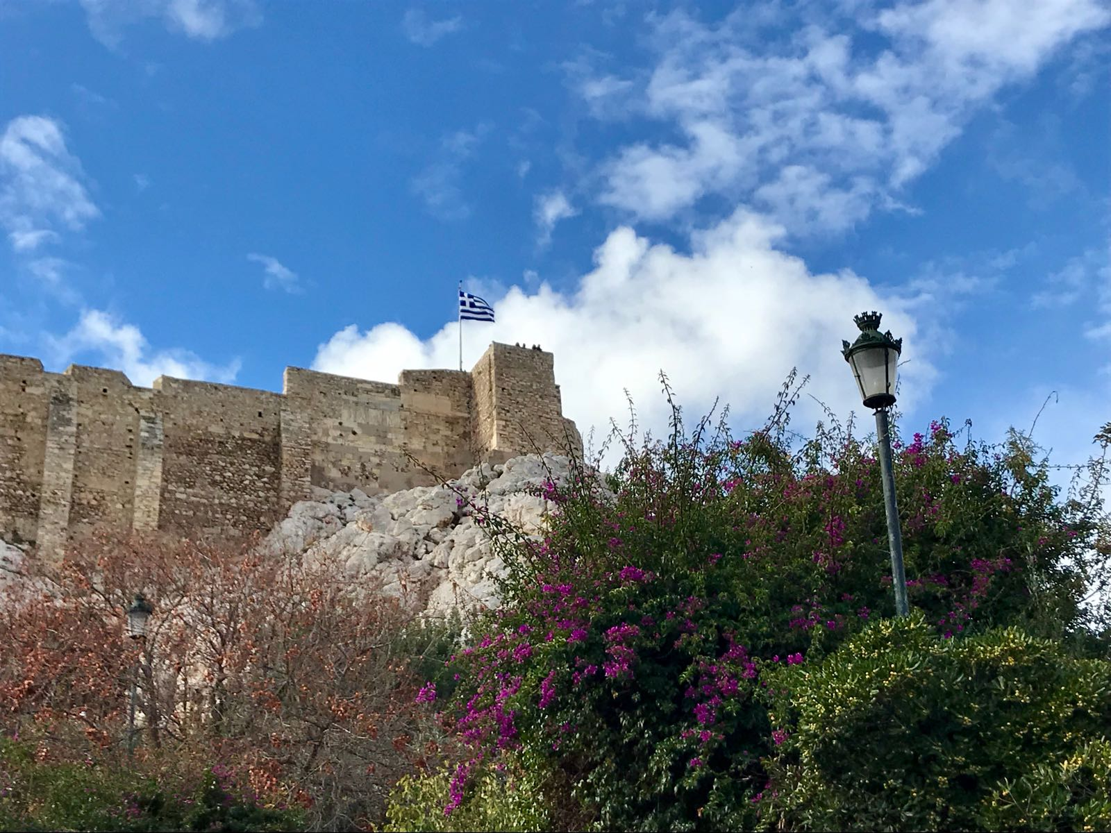 View of the Acropolis from below with the Greek flag flying