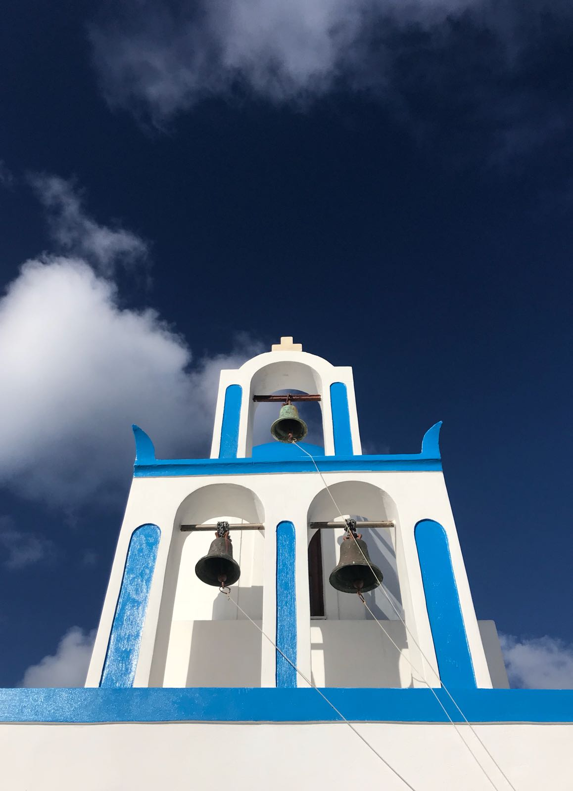 Two level blue and white bell tower against a blue sky