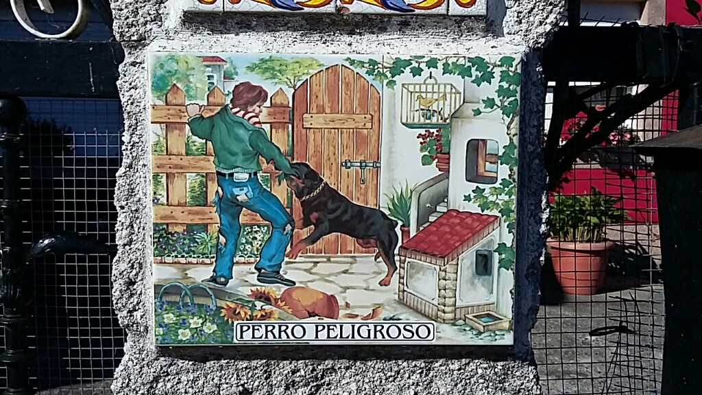 Ceramic tile with a picture of a man being attacked by a rottweiler outside a pleasant cottage