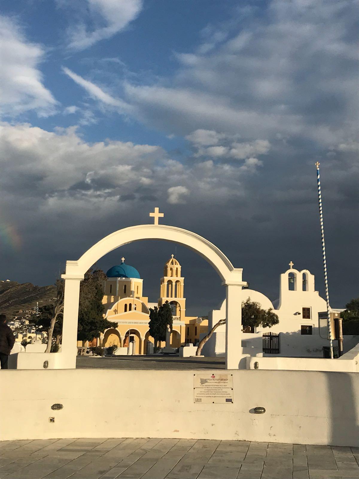 Light ochre church in Santorini at sunset, viewed through a white arch