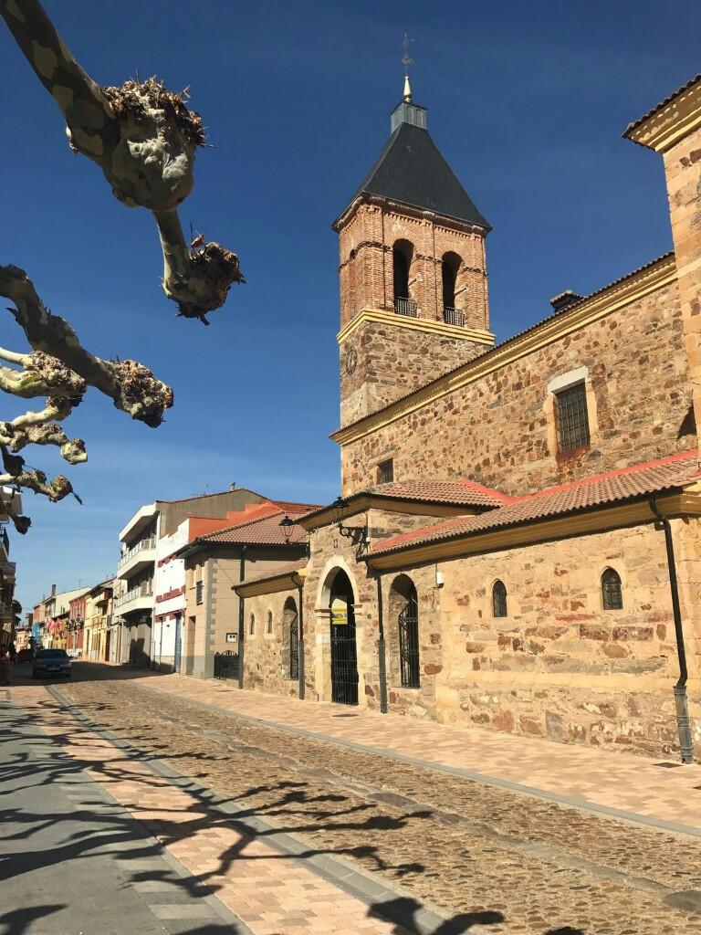 Church in Hospital de Orbigo next to shadows of trees pruned for autumn