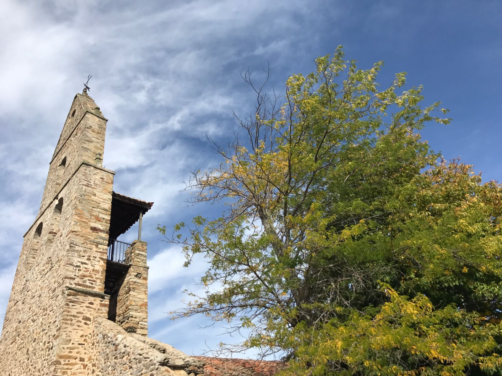 Church in Rabanal with bell tower in front of a blue sky