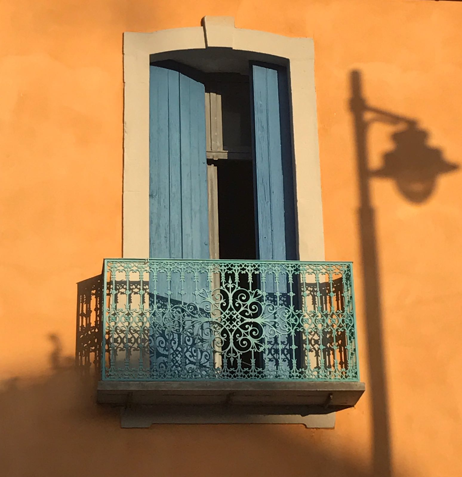 Balcony in Marseillan with blue railings and shutters against a yellow building