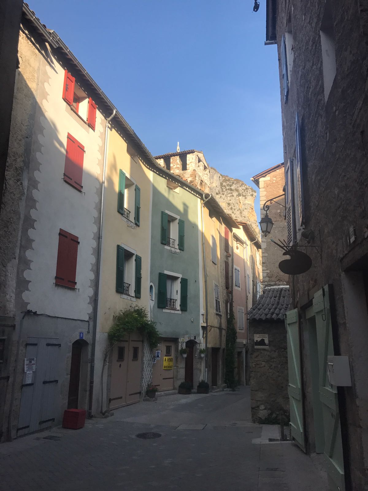 A street in Castellane, each house a different colour, with an artist's studio marked by a sign the shape of an easel