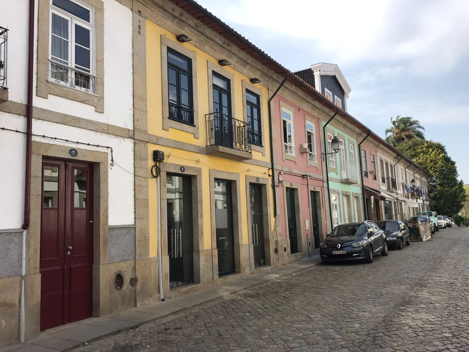 A colourful street in Ponte de Lima, with houses in white, pink, yellow and green