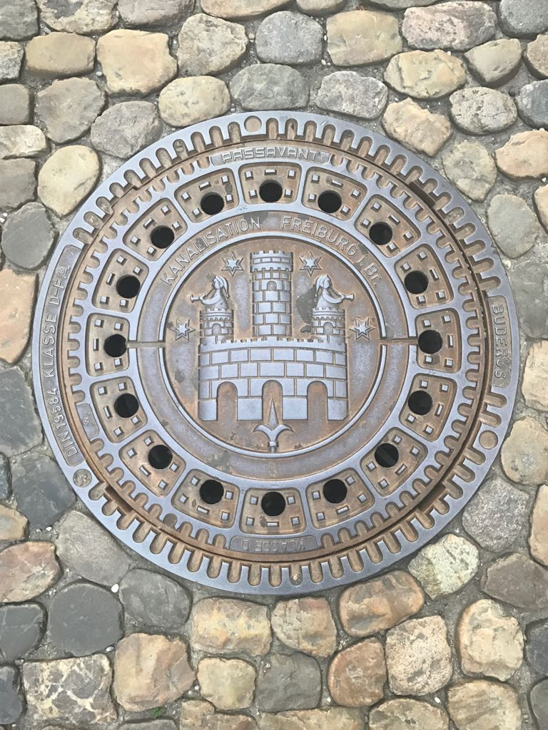 manhole cover with a castle and two trumpeters