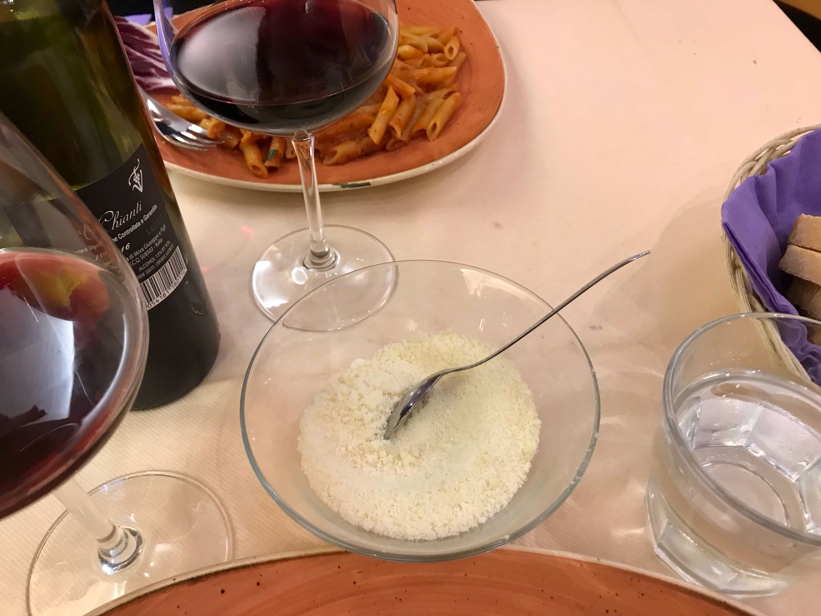 A bowl of parmesan on our dinner table between two glasses of wine