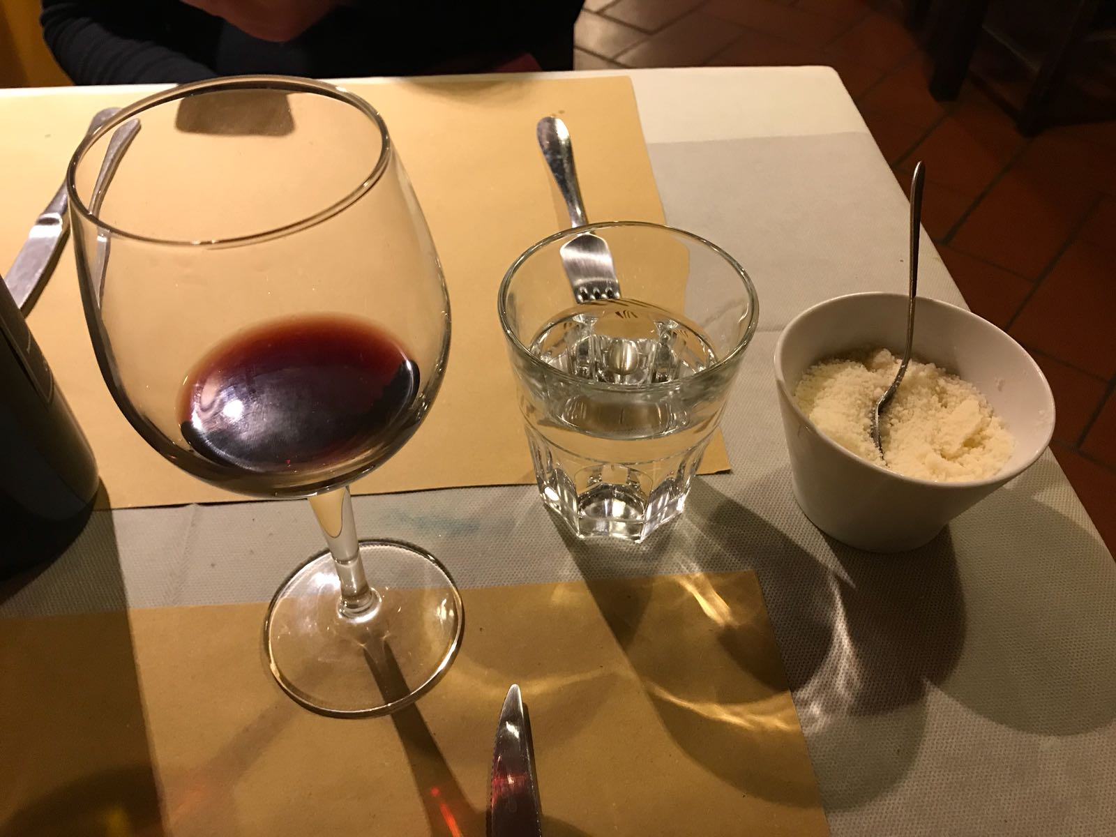 A bowl of parmesan on our dinner table alongside glasses of wine and water