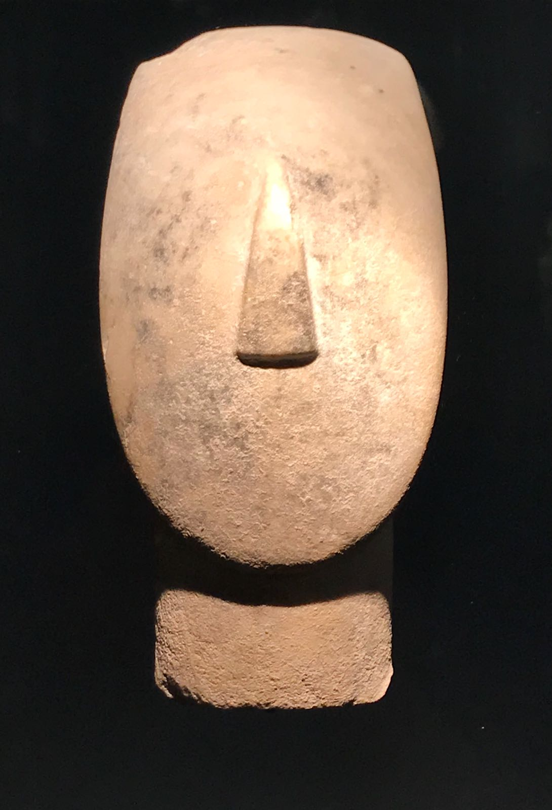 Head of a sculpture from ancient Greece with a featureless face and triangular nose