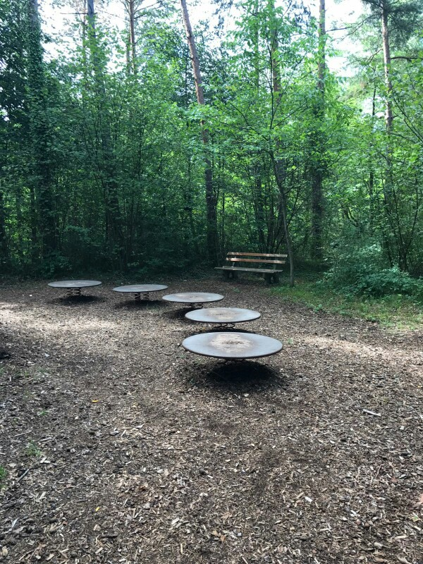 a series of big wooden discs each sitting on a solitary red spring