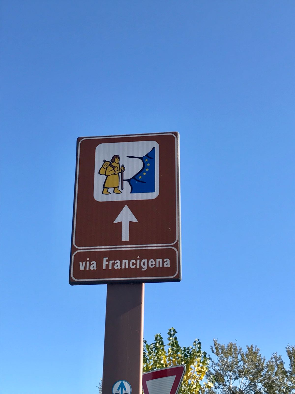 Francigena road sign showing the logo for the route of a cartoon pilgrim next to some of the EU stars
