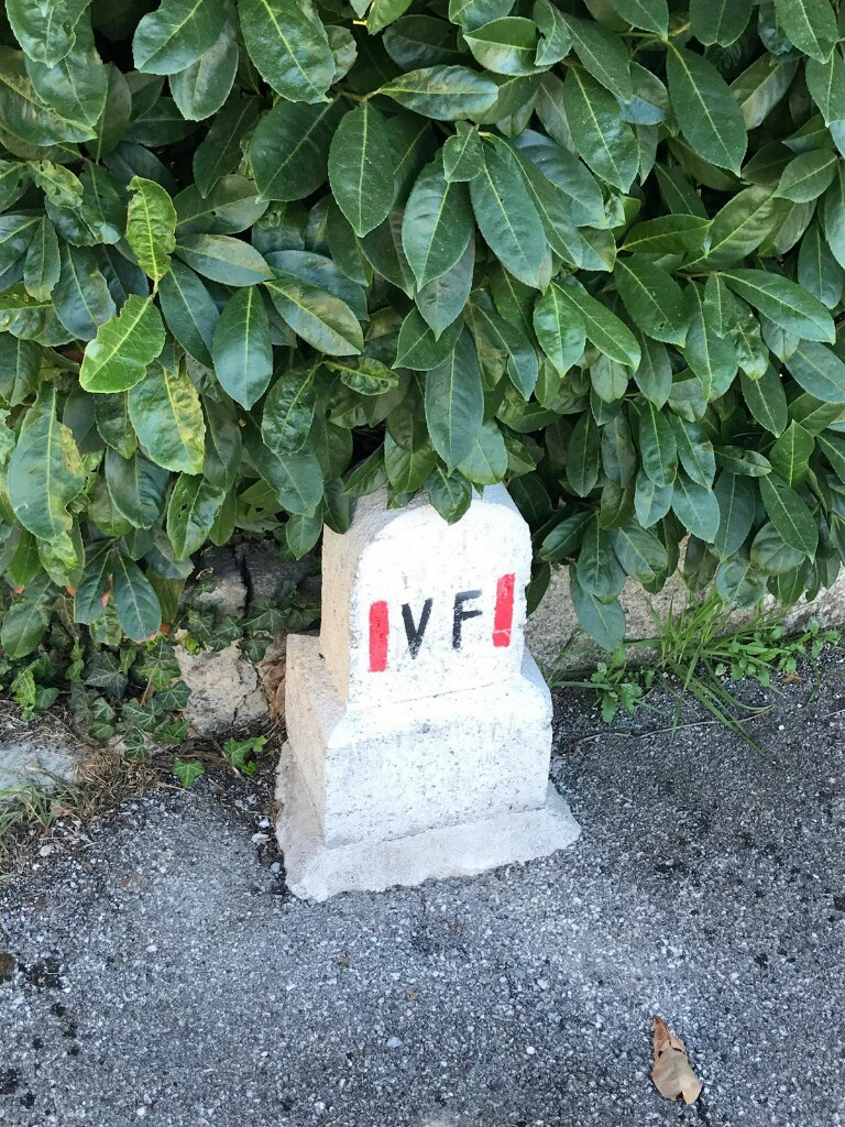 Stone marker with the letters V and F, on white between two red vertical bars