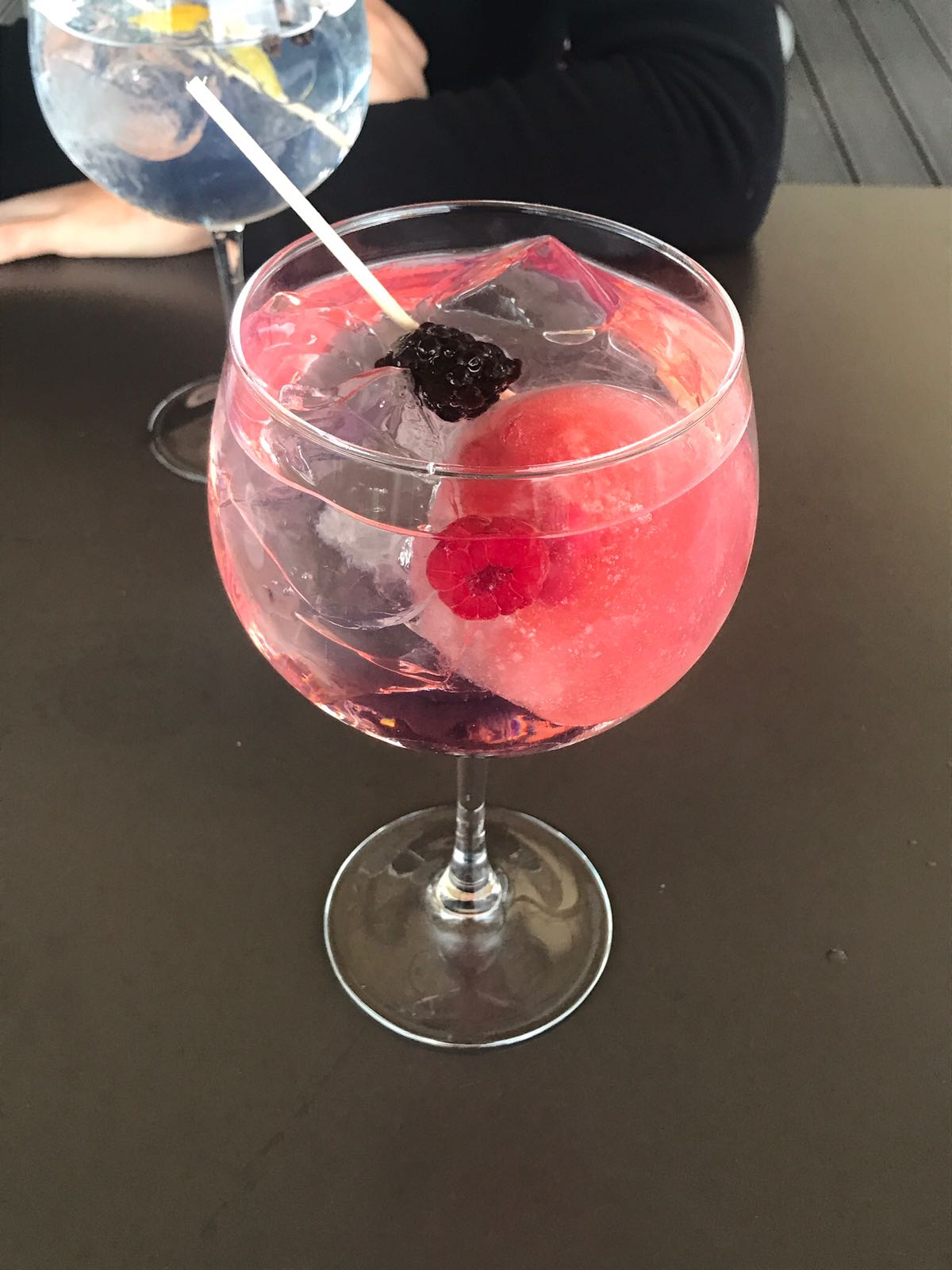 Pink gin and port cocktail in a massive glass with a raspberry and a blackberry in