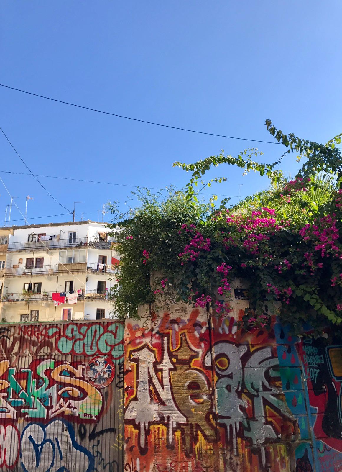 Wall of graffiti alongside the top of a tower block below a blue sky