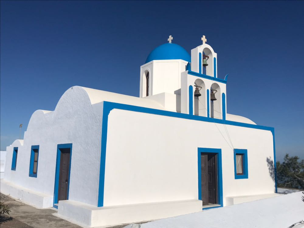 White church made of smoothed cubic shapes and domes with blue edging and blue dome
