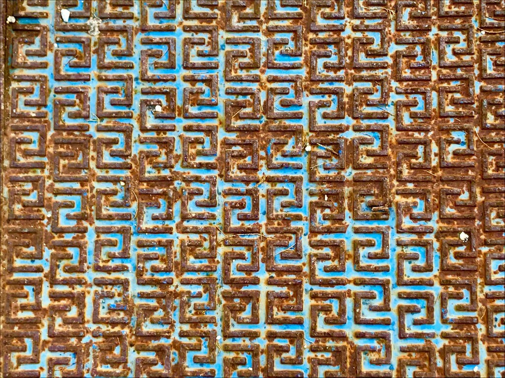 Light blue metal plate with embossed pattern of square spirals rusted brown
