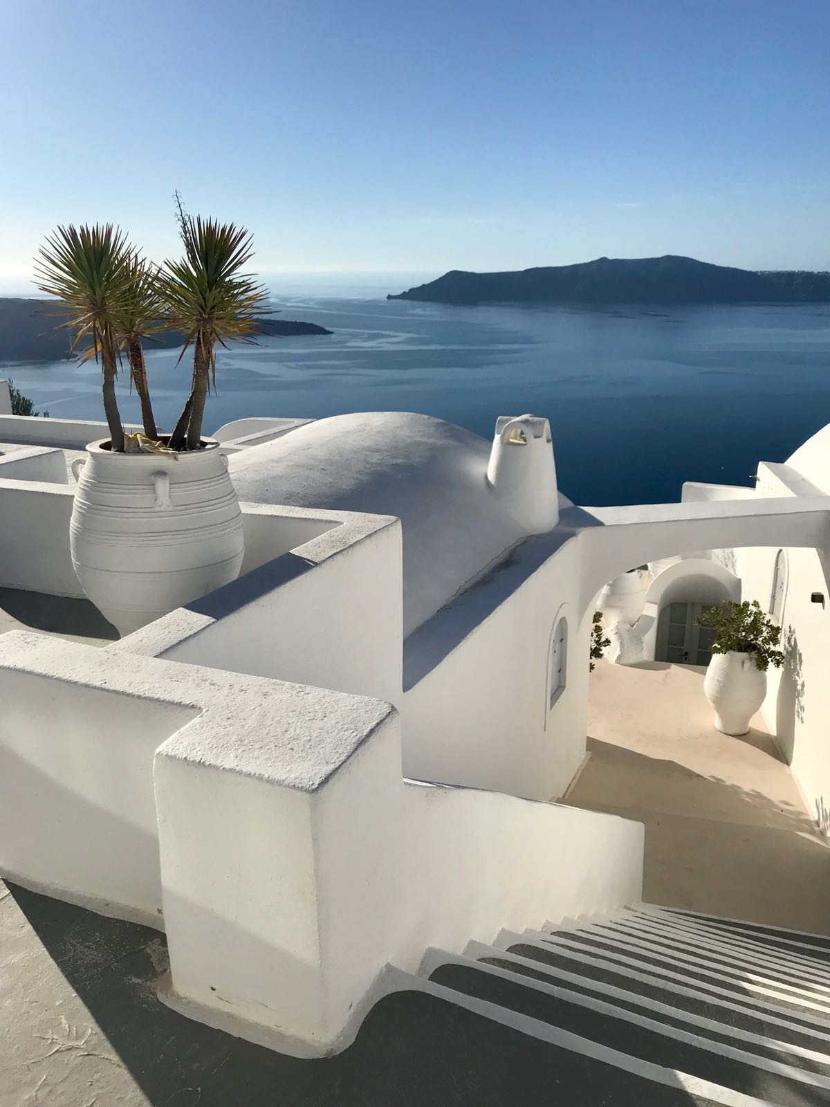Maze-like white houses in Santorini divided by pathways and roofed by domes