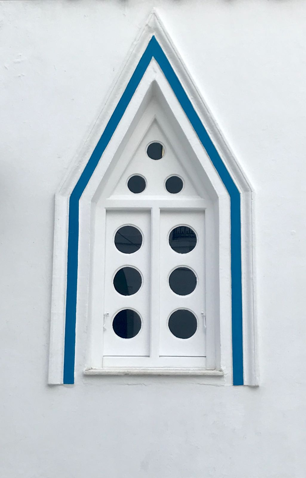 Triangular window frame surrounding opaque shutters each inset with circular holes
