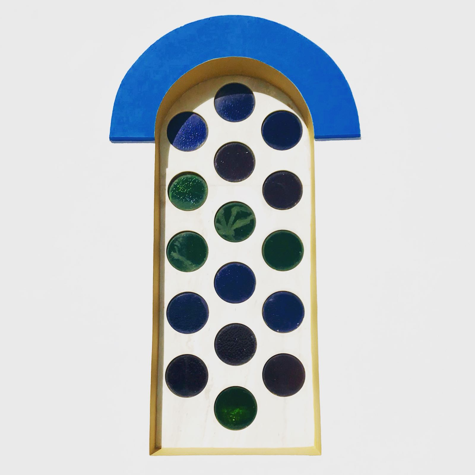 Window with blue arch frame surrounding an opaque pane inset with transparent circles