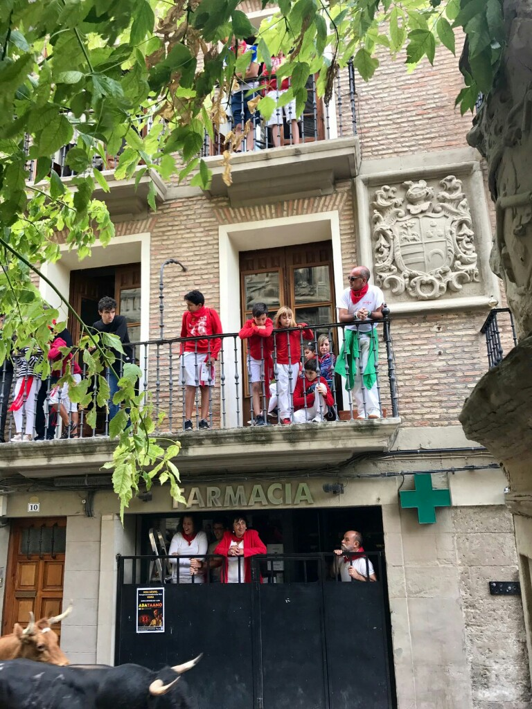 A local family watching the bulls run in the street below from their balcony