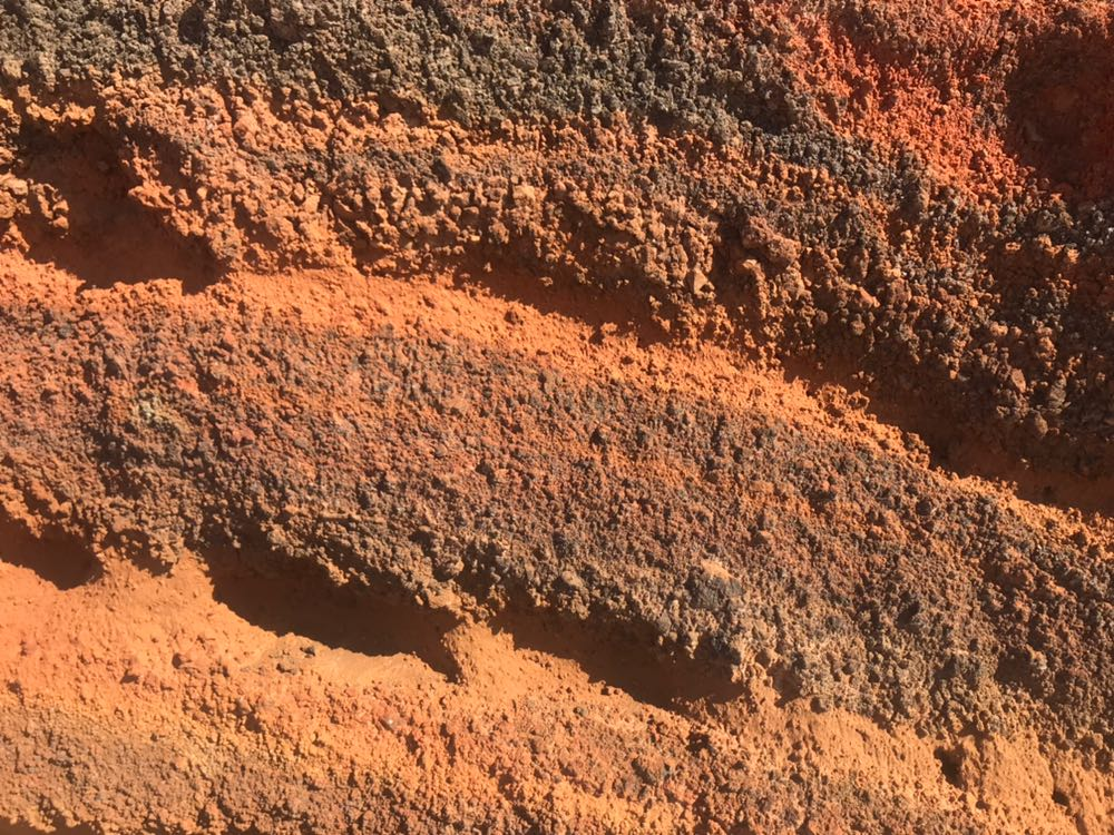 Close up of the cliffside rock on Santorini showing the different coloured layers of rock