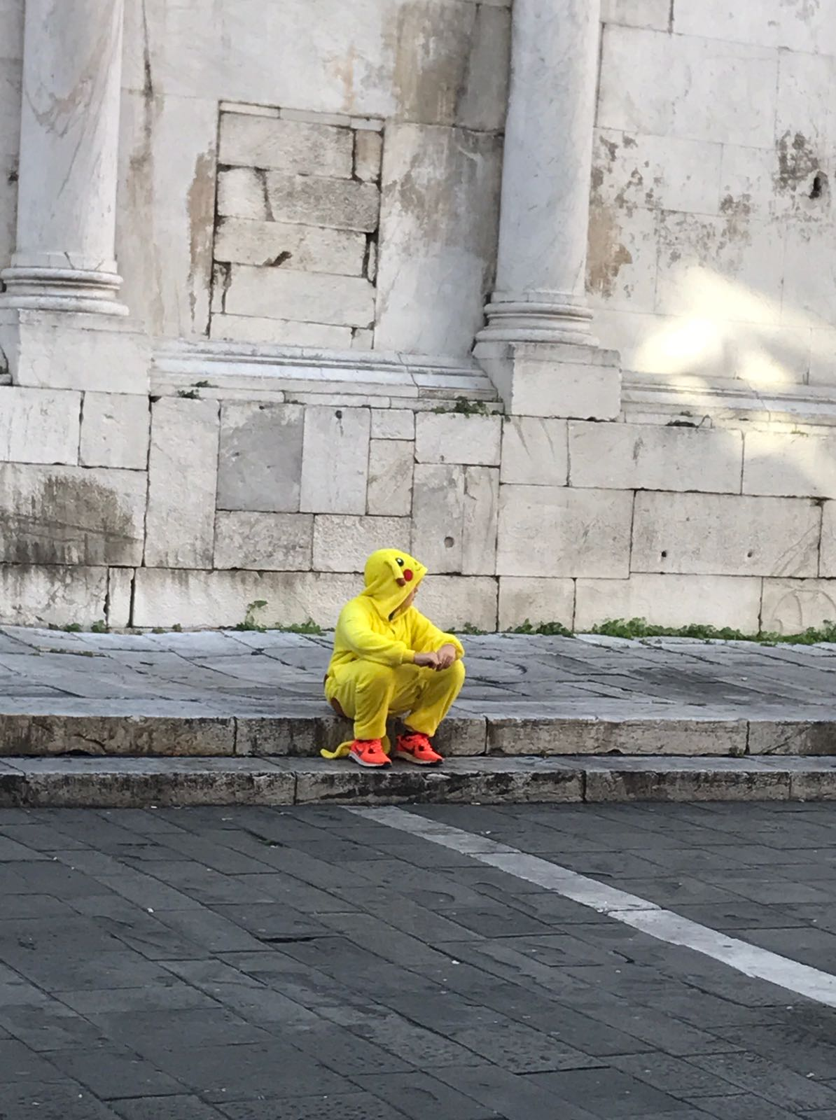 Kid dressed in a pikachu onesie sitting on its own next to a church