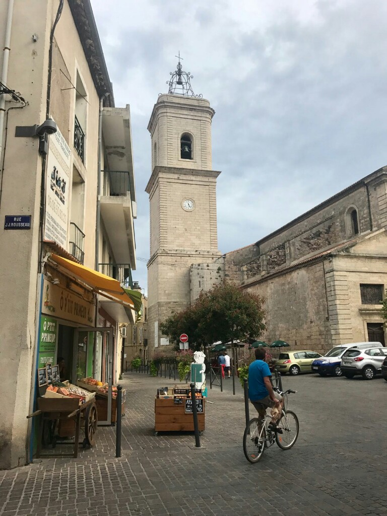 The church in Marseillan with a man on a bike in the foreground