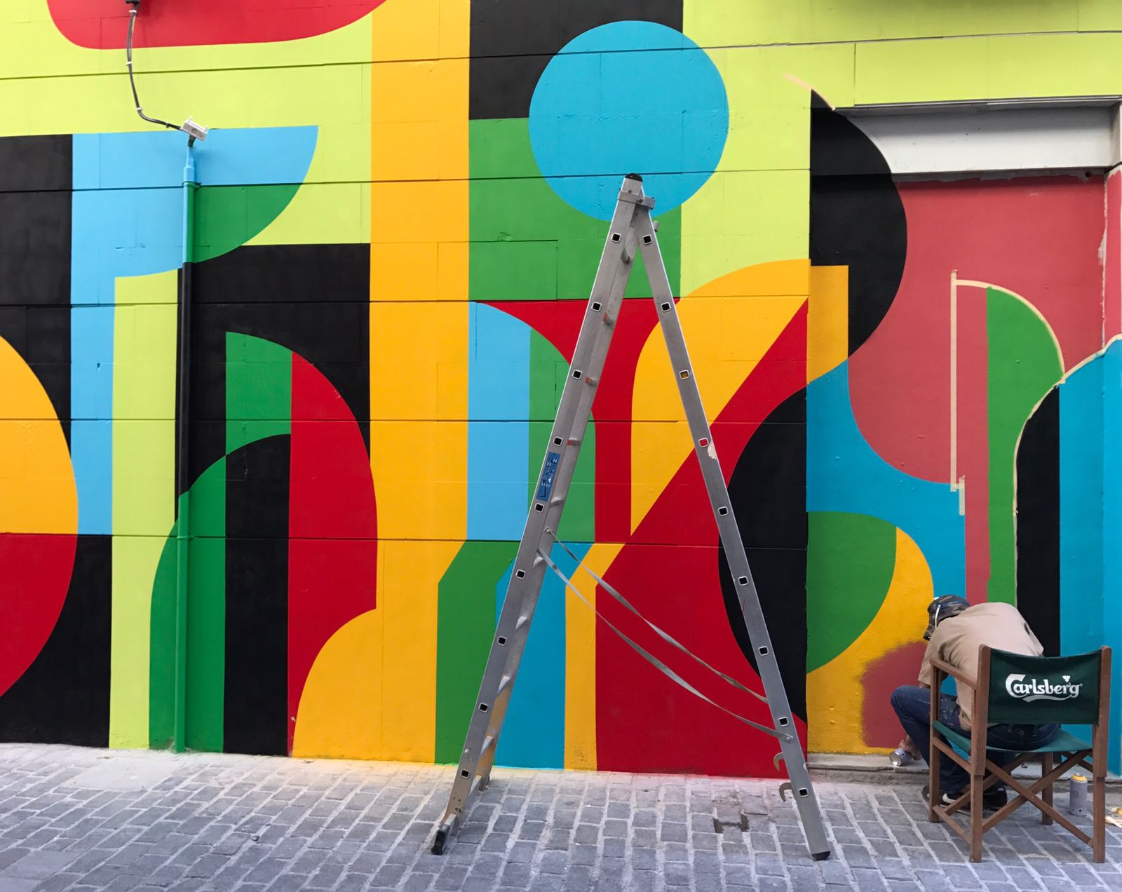 Geometric mural still being painted with the artist at work