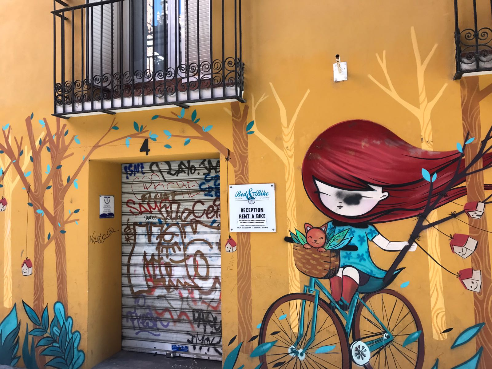 Mural of manga girl on bike cycling through trees with tiny houses tied to them